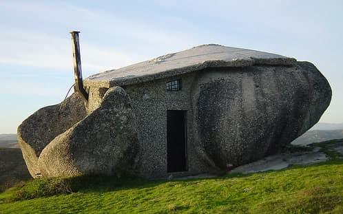 casa de piedra y madera hecha entre grandes rocas