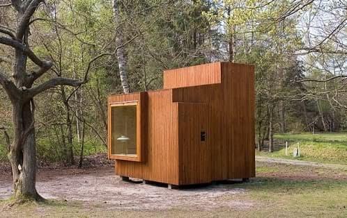 refugio de madera con cama y libreria